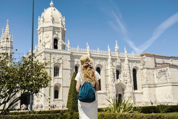 Foto da paisagem de uma jovem viajante apreciando a vista no mosteiro dos jerônimos, em lisboa, portugal