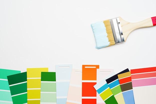 Foto da paleta com cores azuis e verdes, vermelhas, pincel, sobre fundo branco em branco ... lugar para texto.