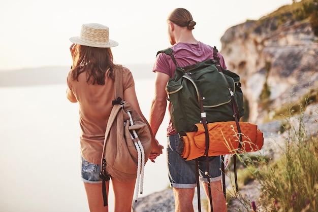 Foto da parte de trás. o jovem casal decidiu passar as férias de forma ativa na beira de uma linda rocha com um lago ao fundo.