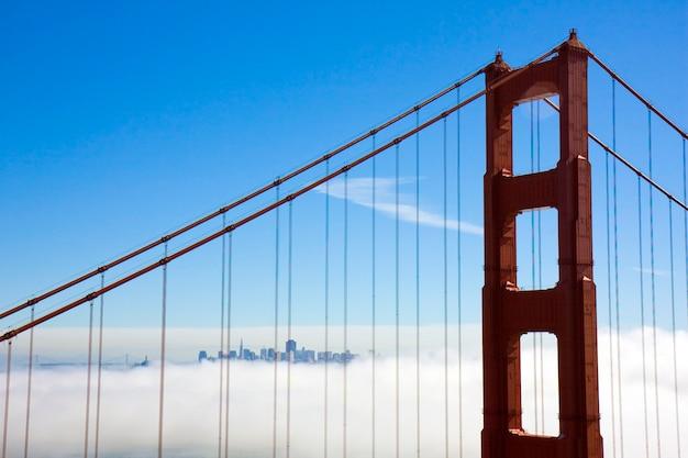 Foto da ponte golden gate com são francisco à distância, cercada por nuvens