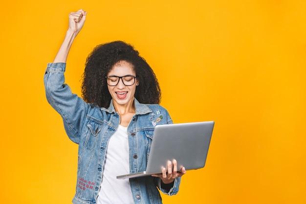 Foto da posição alegre afro-americano nova da mulher de negócio isolada sobre o fundo amarelo com computador portátil. olhar de lado faz um gesto vencedor.