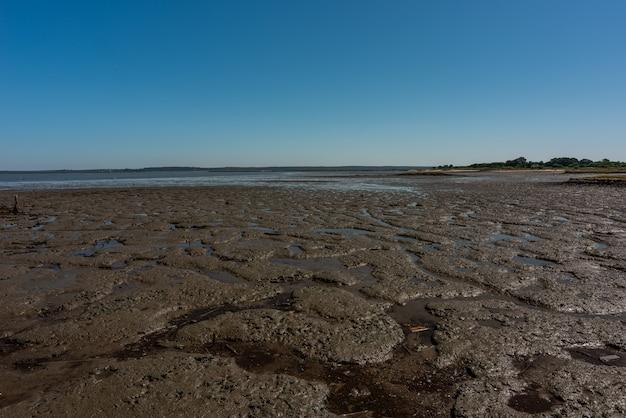 Foto da praia de areia seca no cais palafítico da carrasqueira, portugal durante a maré baixa
