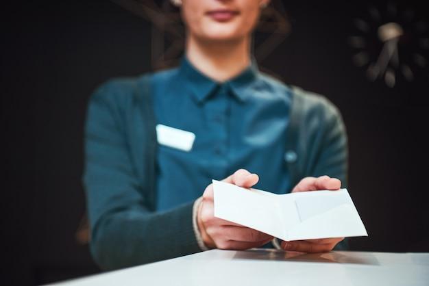 Foto da recepcionista entregando o cartão-chave a um cliente no hotel