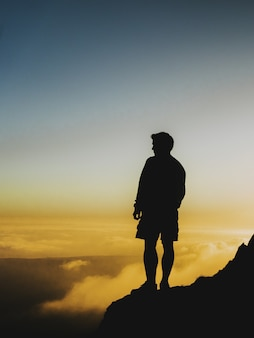 Foto da silhueta de um homem parado em um penhasco olhando o pôr do sol