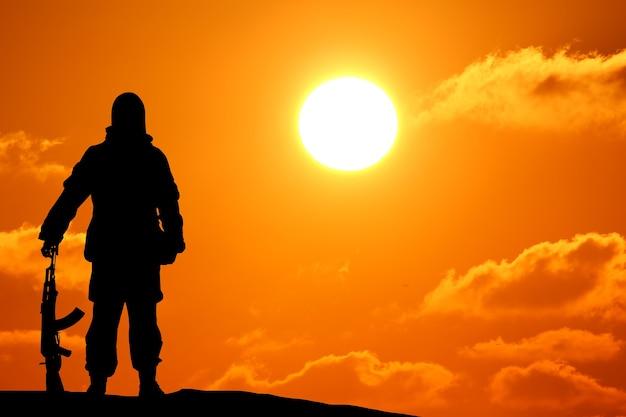 Foto da silhueta de um soldado segurando uma arma com um céu colorido e uma montanha no fundo