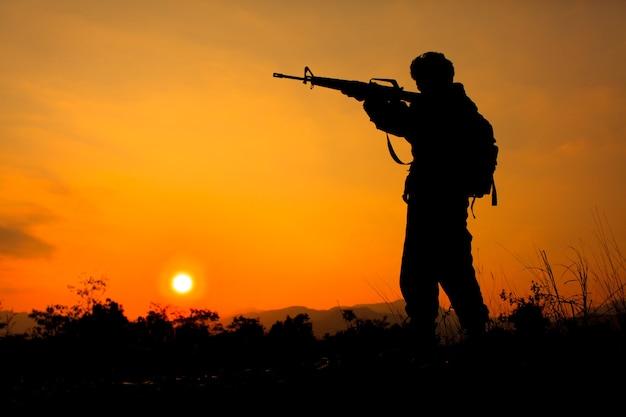 Foto da silhueta de um soldado segurando uma arma