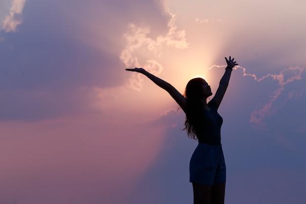 Foto da silhueta de uma mulher asiática confiante e feliz, levantando as mãos