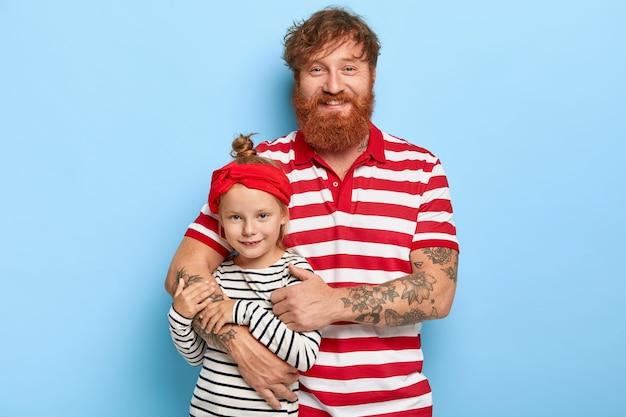 Foto da simpática e elegante filha ruiva e do pai posando juntos