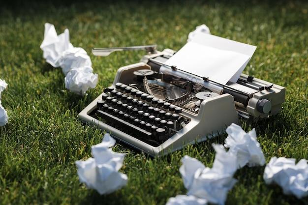 Foto da velha máquina de escrever em uma grama verde com uma folha de papel.