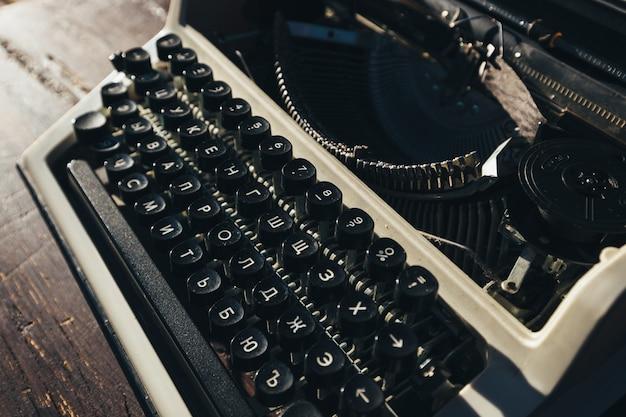 Foto da velha máquina de escrever na mesa de madeira na luz do sol, look retro.