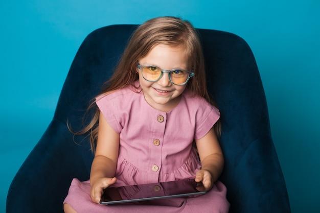 Foto da vista frontal de uma garota caucasiana com óculos amarelos sorrindo para a câmera enquanto está sentada na poltrona
