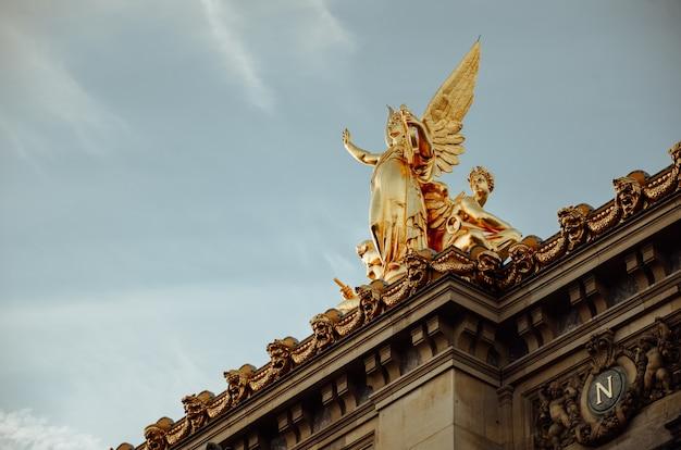 Foto da vista inferior da estátua dourada de uma mulher com asas em paris, frança