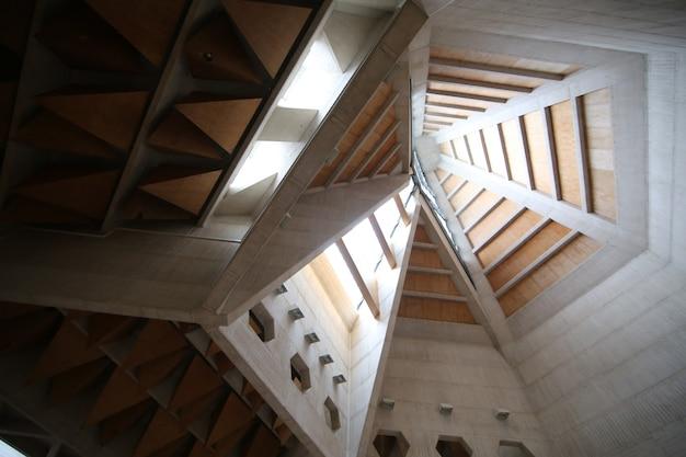 Foto da vista inferior de um telhado de prédio branco e marrom de dentro