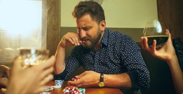 Foto da vista lateral de amigos sentados à mesa de madeira. amigos se divertindo enquanto jogam o jogo de tabuleiro.
