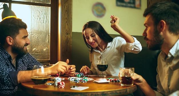 Foto da vista lateral de amigos sentados à mesa de madeira.