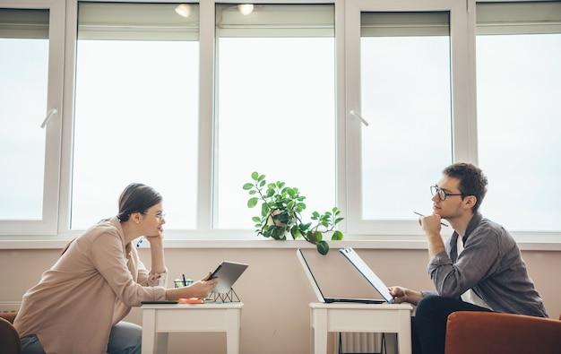 Foto da vista lateral de um casal caucasiano olhando um para o outro e pensando enquanto trabalham com o laptop