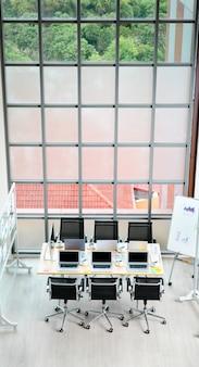 Foto da vista superior da mesa da sala de reuniões em um escritório vazio da empresa, cheio de computadores portáteis, copos de café, documentos de papelada de dados, cadeiras pretas e placa de vidro perto de janelas de vidro de construção.
