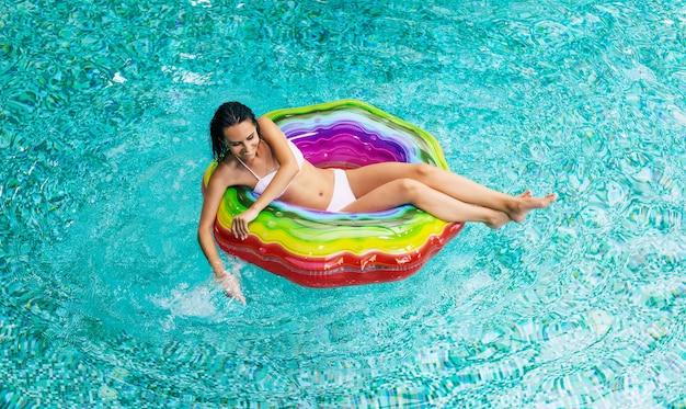 Foto da vista superior de curtir o bronzeado animado mulher de biquíni no colchão inflável na piscina. férias de verão. relaxar na piscina do hotel
