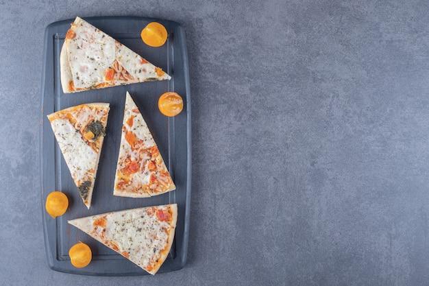 Foto da vista superior de fatias de pizza margarita na placa de madeira cinza.