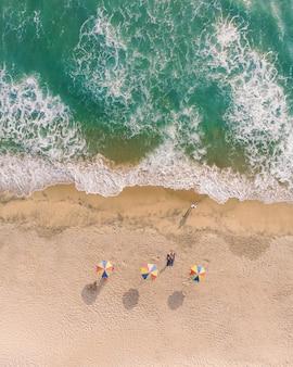 Foto da vista superior de guarda-sóis e pessoas deitadas na areia na praia de varkala