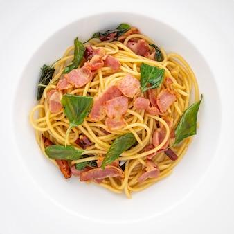 Foto da vista superior de macarrão espaguete com pimenta seca, alho, manjericão e bacon em um fundo de textura de placa de cerâmica branca, proporção quadrada