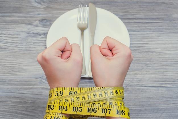 Foto da vista superior de mãos com punhos amarrados com fita métrica sobre o prato, garfo e faca
