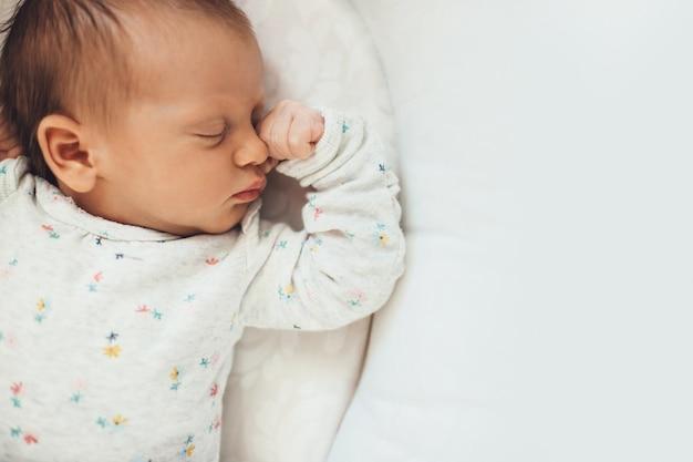Foto da vista superior de um bebê recém-nascido dormindo bem na cama perto do espaço livre