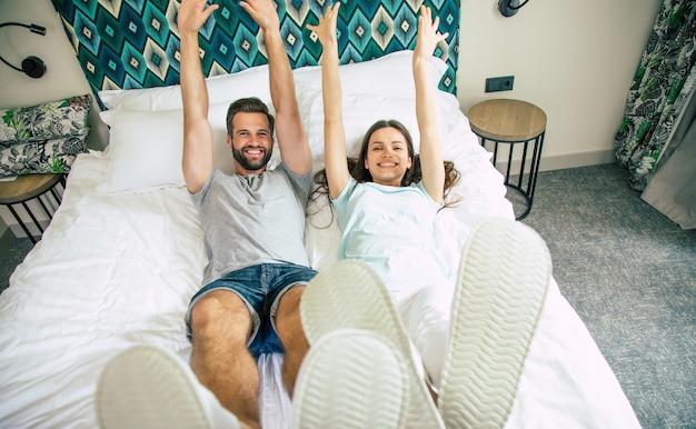 Foto da vista superior de um casal feliz, animado e engraçado, deitado na cama em um quarto de hotel