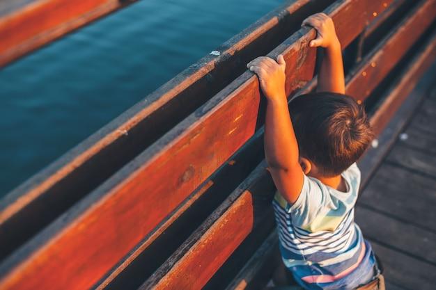 Foto da vista superior de um menino caucasiano posando em uma ponte enquanto olha para o lago