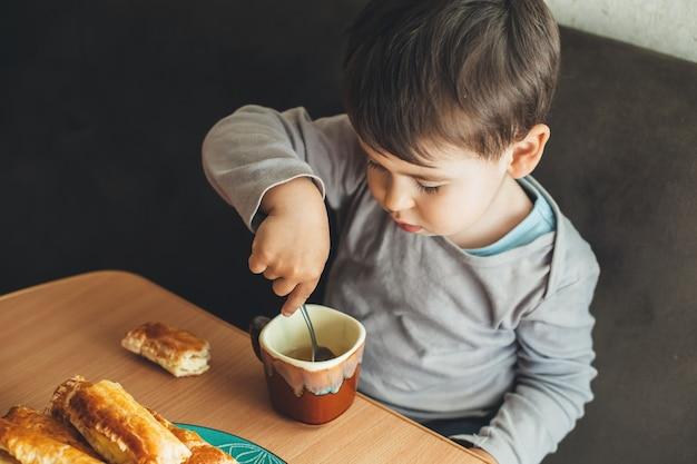 Foto da vista superior de um menino caucasiano sentado à mesa e bebendo um chá com uma colher enquanto come biscoitos