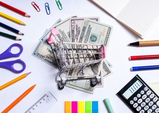 Foto da vista superior de um pequeno carrinho de compras com dólares no centro e material de escritório colorido, isolado no branco.