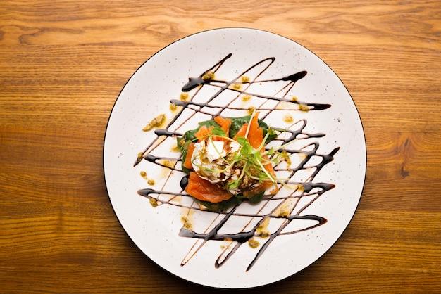 Foto da vista superior de um prato com um sanduíche de salmão em uma mesa de madeira