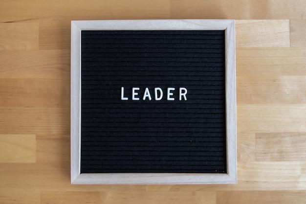 Foto da vista superior de um quadro-negro com a citação do líder em uma mesa de madeira