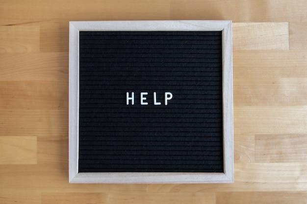 Foto da vista superior de um quadro negro com citação de ajuda em uma mesa de madeira