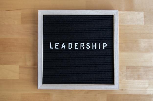 Foto da vista superior de um quadro-negro com citação de liderança em uma mesa de madeira