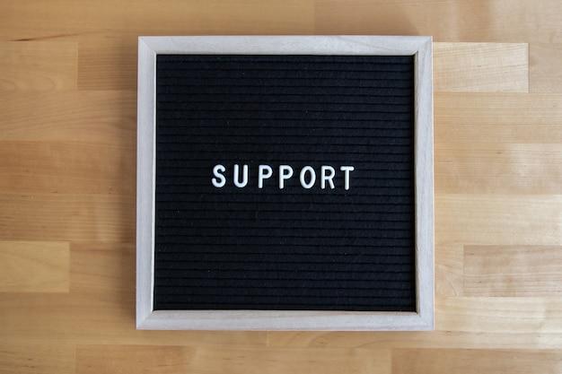 Foto da vista superior de um quadro-negro com orçamento de apoio em uma mesa de madeira