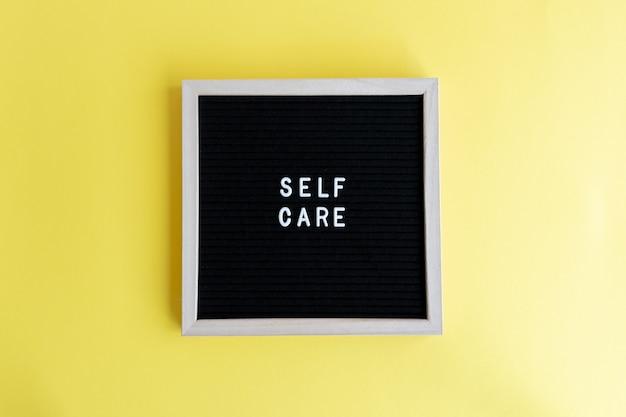 Foto da vista superior de um quadro negro com uma massagem de autocuidado em um fundo amarelo