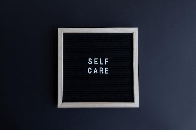 Foto da vista superior de um quadro negro com uma massagem de autocuidado em um fundo preto