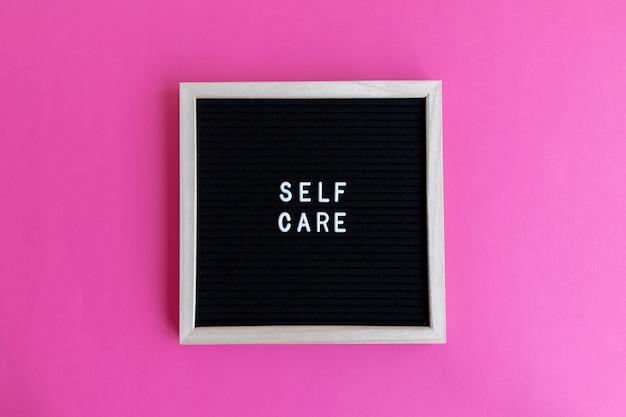 Foto da vista superior de um quadro negro com uma massagem de autocuidado em um fundo rosa