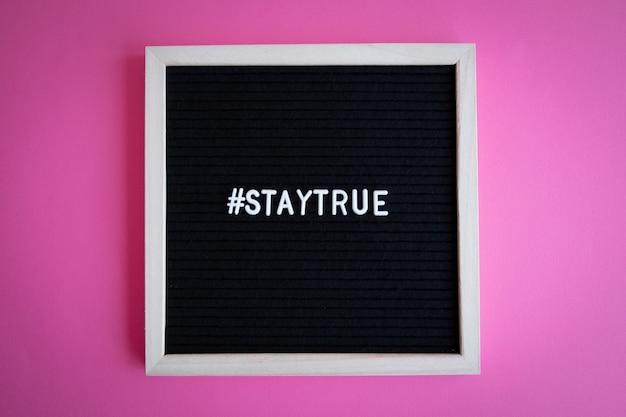 Foto da vista superior de um quadro-negro com uma moldura branca com uma hashtag staytrue em um fundo rosa