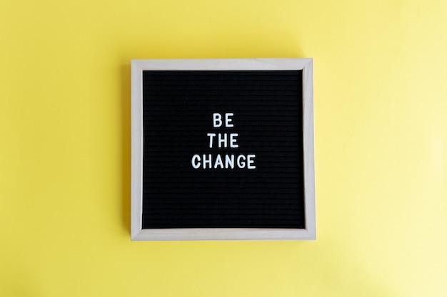 Foto da vista superior de um quadro-negro com uma moldura branca e uma massagem be the change em um fundo amarelo