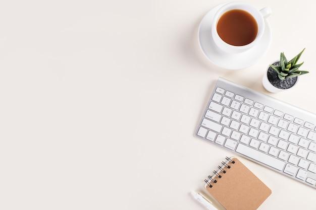Foto da vista superior de um teclado, bloco de notas, caneta, uma xícara de café quente e uma planta na mesa branca