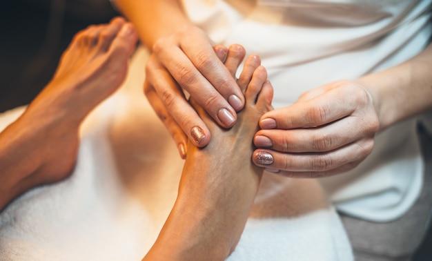 Foto da vista superior de um trabalhador do spa fazendo uma sessão de massagem nos pés no salão do spa com uma jovem cliente