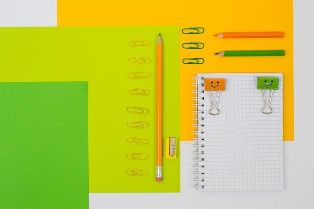 Foto da vista superior do caderno espiral, lápis, clipes, pastas
