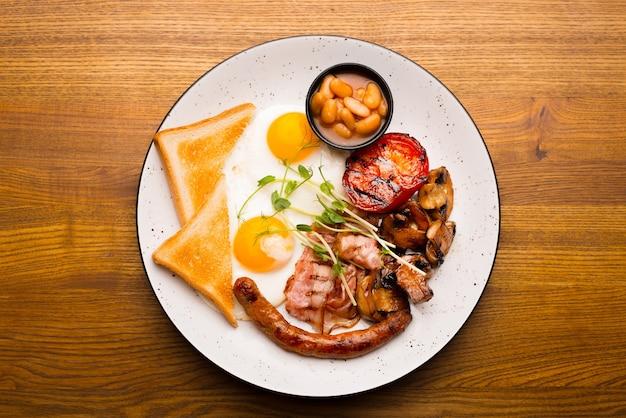 Foto da vista superior do saboroso café da manhã inglês em restaurante sobre mesa de madeira