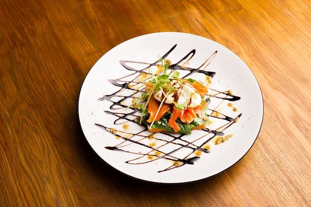 Foto da vista superior lateral de um prato com um saboroso sanduíche de salmão.