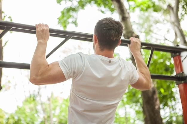 Foto da vista traseira de um atleta do sexo masculino fazendo flexões, malhando ao ar livre