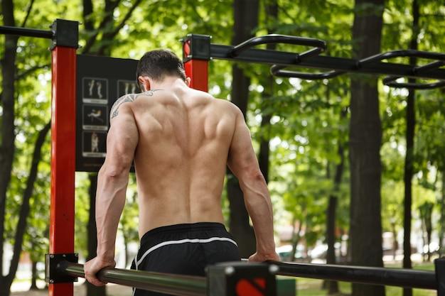 Foto da vista traseira de um homem atlético machucado fazendo tríceps ao ar livre, copie o espaço