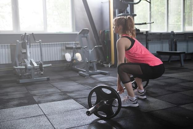 Foto da vista traseira de uma esportista fazendo exercícios de levantamento terra com barra na academia, copie o espaço