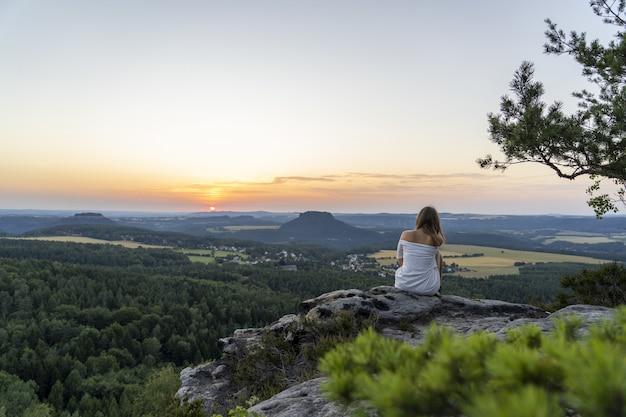 Foto da vista traseira de uma jovem mulher sentada na beira de um penhasco, apreciando um pôr do sol majestoso